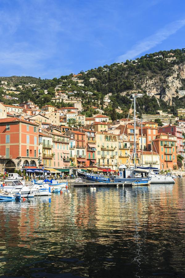 Villefrance, France, seafront buildings and boats with reflections in water. Villefrance, France, seafront buildings and boats in bright sunlight  with stock photo