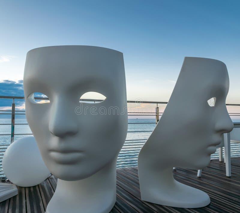 Villeneuve-Loube, Frankrijk - September 2018 Twee grote plastic maskers bevinden zich op het balkon van het restaurant op het str royalty-vrije stock fotografie