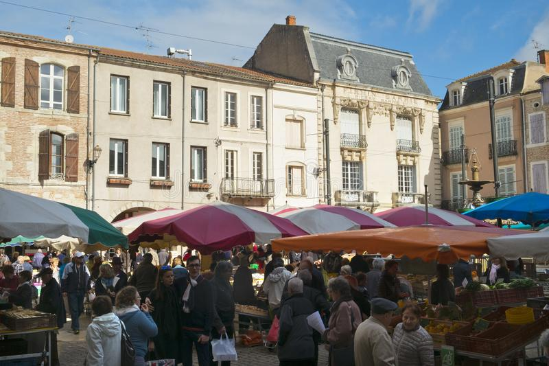 Spring sunshine, Saturday market, Villeneuve-sur-Lot,  France. Villeneuve-sur-Lot, France - 1st April 2017: Shoppers brave a chilly spring morning at the royalty free stock images