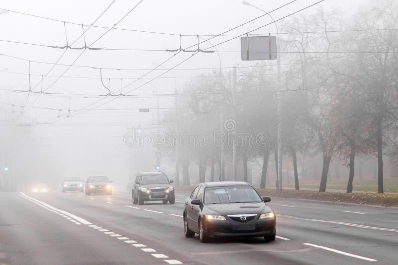 VILNA, LITUANIA - 21 DE OCTUBRE DE 2018: Niebla pesada de la mañana en calle de la ciudad Tráfico por carretera foto de archivo