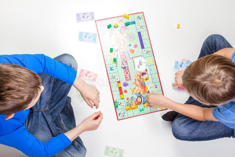 Vilnius Litauen - 23 April 2017: Barn som spelar monopol för brädelek royaltyfri bild
