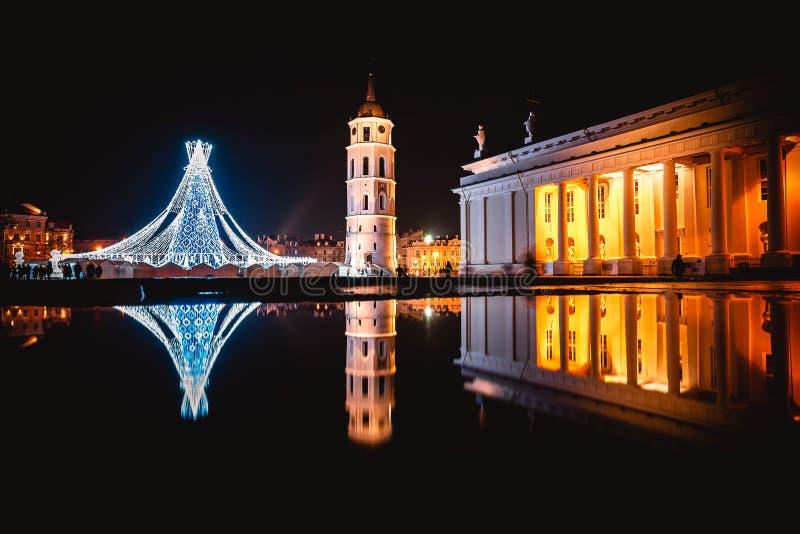 VILNIUS, LITAUEN - 10. DEZEMBER 2019: Weihnachtsbaum in Form einer Schachkönigin auf dem Platz der Kathedrale und deren Reflexion lizenzfreie stockfotografie
