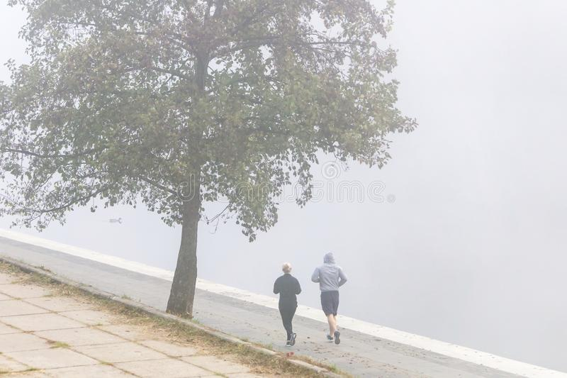 VILNIUS, LITAUEN - 21. OKTOBER 2018: Verbinden Sie die Läufer, die Stoß im Morgennebel durch Flussufer anstreben lizenzfreie stockbilder