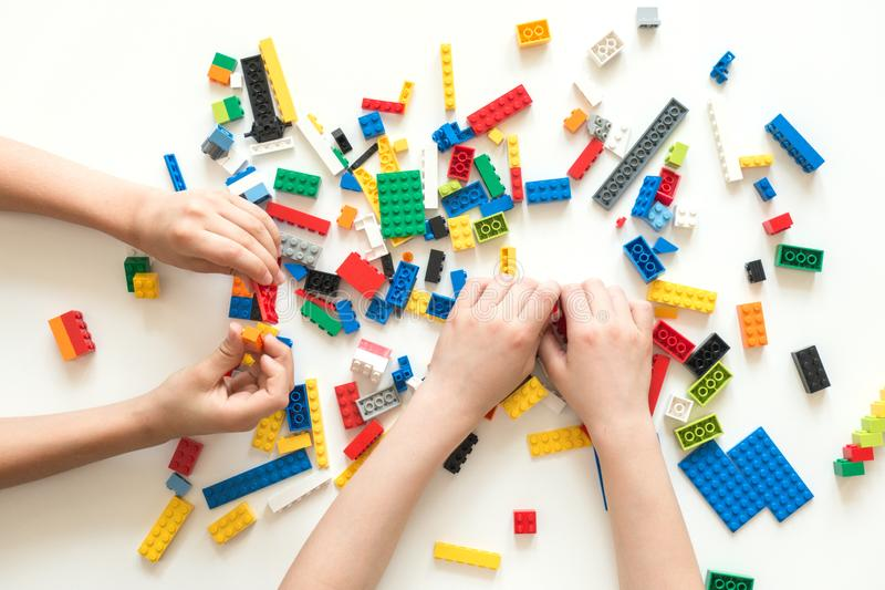 Vilnius, Lithuania - April, 2017. Children hands play with colorful lego blocks on white table. stock photos