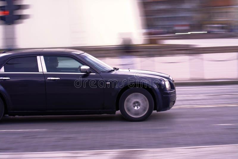 2017-02-25 Вильнюс Литва, черная машина едет по старой городской дороге. 2017-02-25 Вильнюс Литва, поездка на черном автомобиле по старой городской дороге стоковая фотография