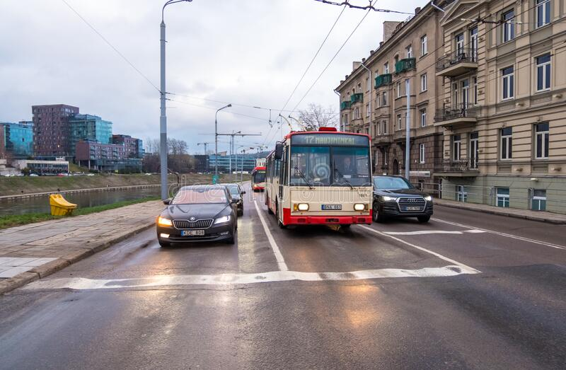 City transport with burning headlights on the road at sunset stock image