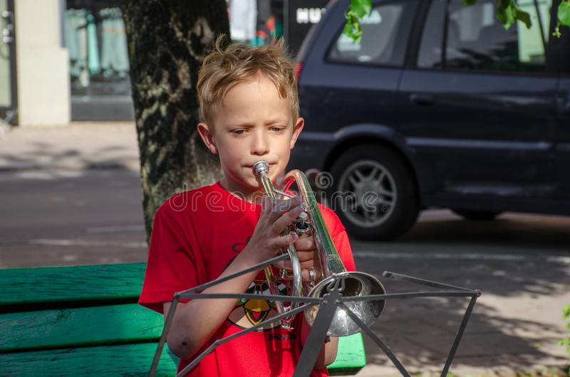 The boy is playing trumpet in street. stock photography