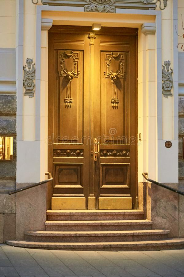 Vilnius, Lithuania - November 5, 2017: Beautiful wooden front door in the evening with illuminated. stock images