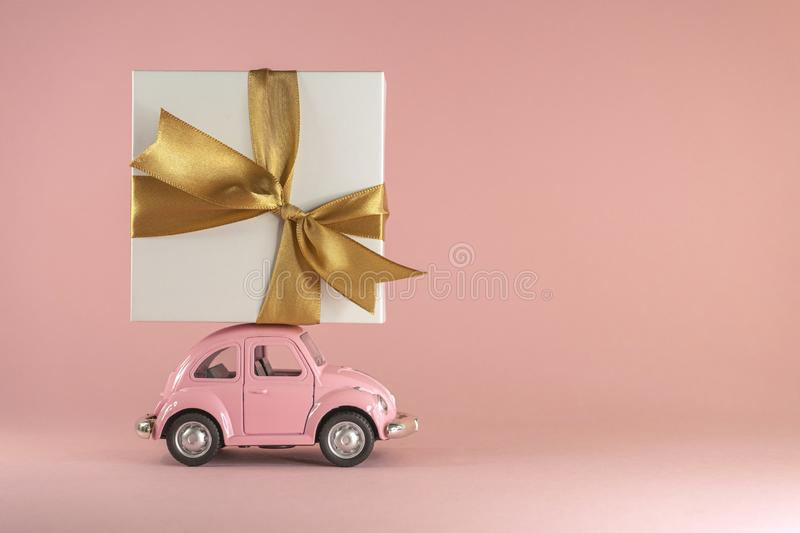 Vilnius, Lithuania - September 09, 2019: Little retro toy model car with present gift box on pastel pink background stock images