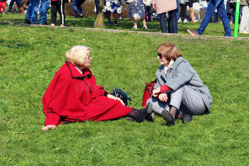 Vilnius, Lithuania - 04 22 2019: Two senior women talking sitting on green grass in Sugihara park stock photo