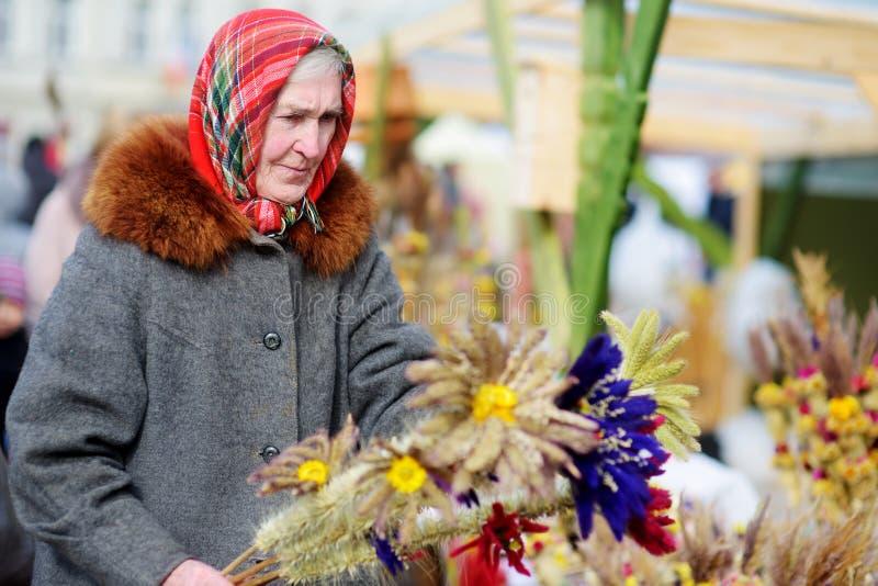 VILNIUS, LITOUWEN - MAART 4, 2016: Hogere vrouw die traditionele met de hand gemaakte Litouwse die Pasen-palm verkopen als verbos stock foto's
