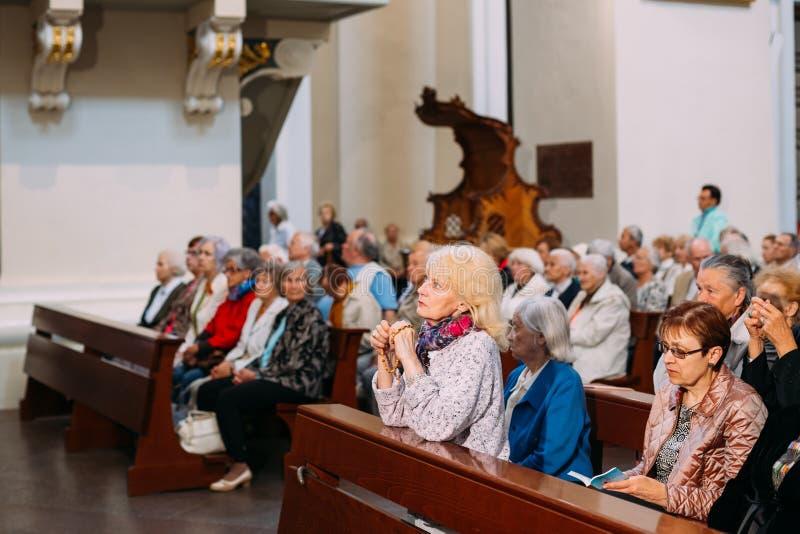 Vilnius, Litouwen Vrouwenparochiaan die in Kathedraalbasiliek bidden stock foto