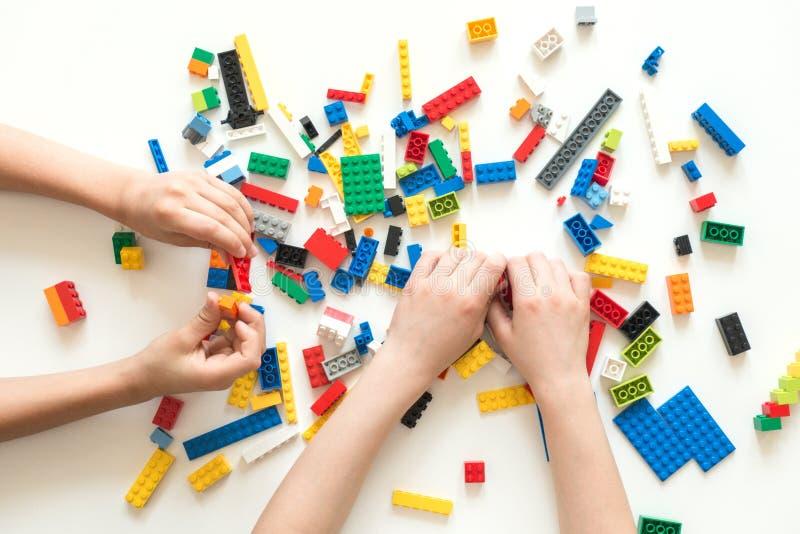 Vilnius, Lituânia - em abril de 2017 As crianças entregam o jogo com blocos coloridos do lego na tabela branca fotos de stock
