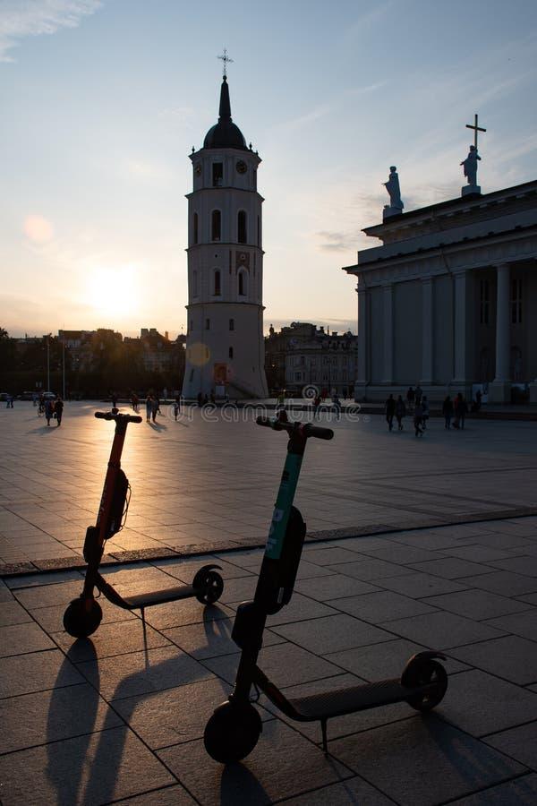 Vilnius, Lituania Sera al quadrato della cattedrale con i motorini elettrici per affitto, immagine stock