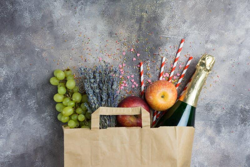 Vin bär frukt, ställer blommor in för partiet, eller picknicken i en packe för pappers- hantverk på grånar konkret bakgrund Top b arkivfoton