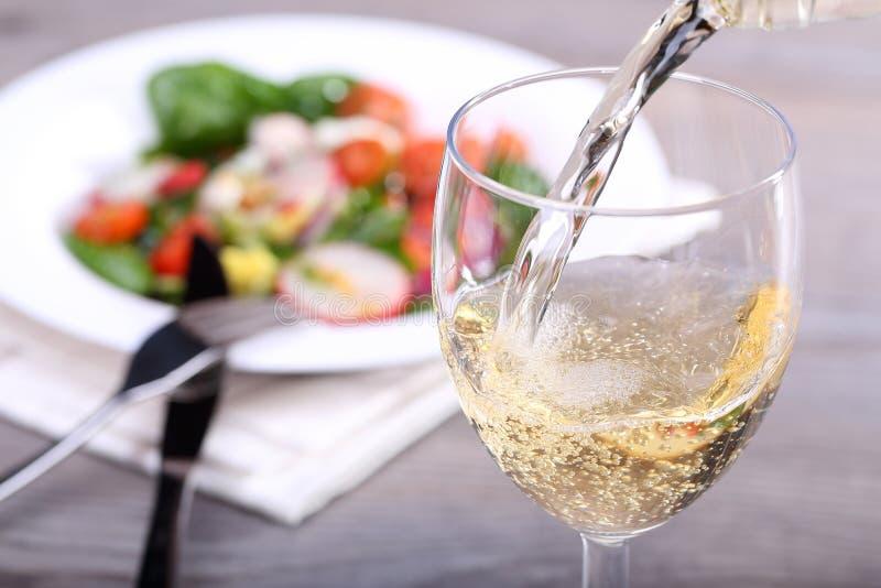 Vin blanc de versement dans le verre images libres de droits
