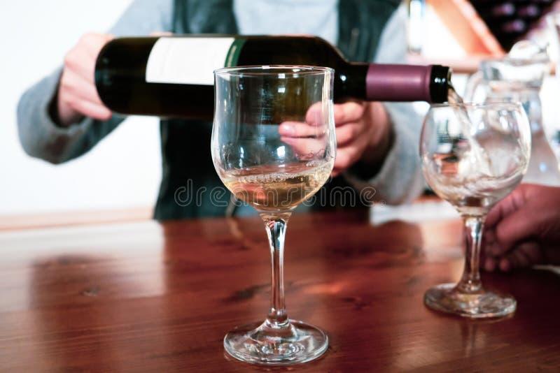 Vin blanc de versement de Sommelier dans un verre photos stock
