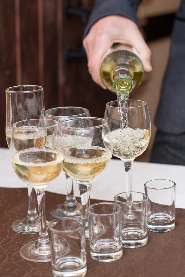 Vin blanc de versement de sommelier masculin dans les verres à vin long-refoulés images stock