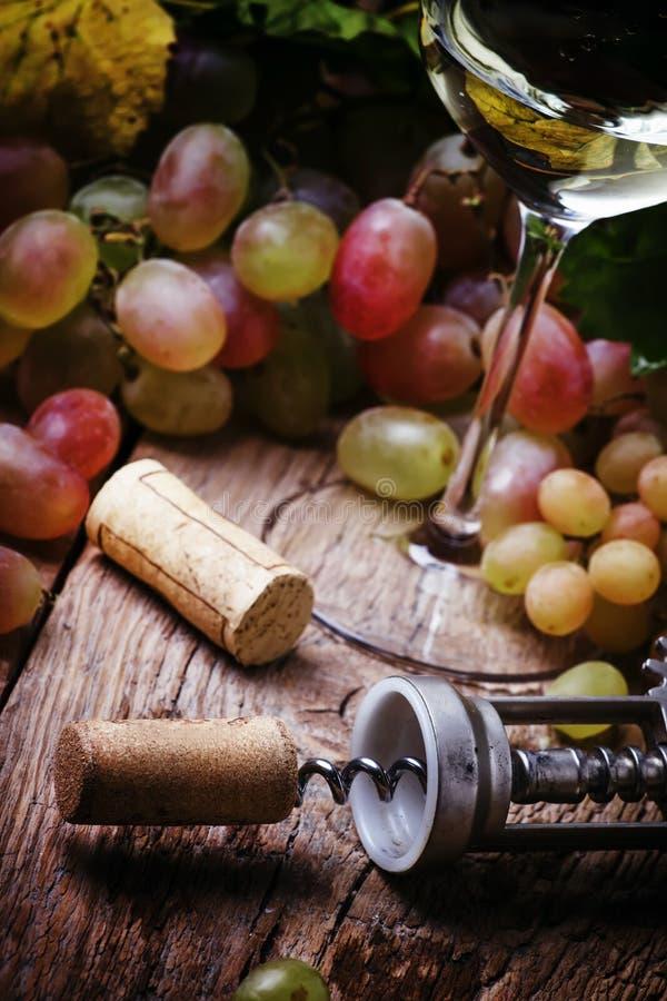 Vin blanc sec dans le verre et le tire-bouchon avec du liège, foyer sélectif photos stock