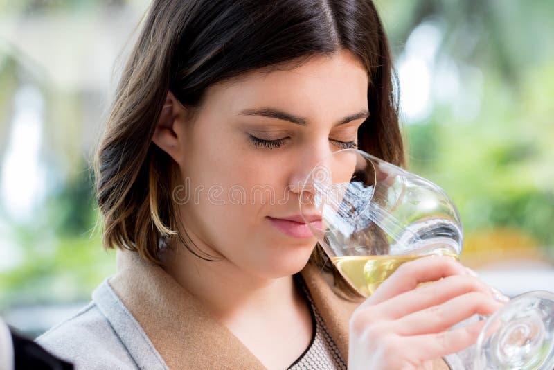 Vin blanc sentant de jeune femme à l'échantillon photographie stock libre de droits