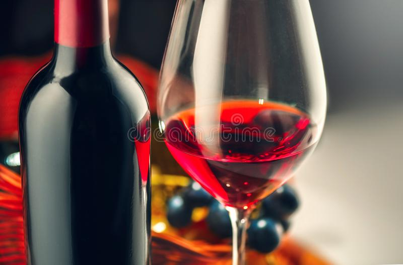 Vin Bouteille et verre de vin rouge avec des raisins m?rs au-dessus du noir photos stock