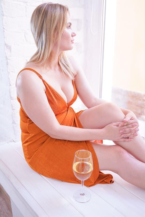 Vin caucasien de boissons de femme de jolie taille plus pendant seul le matin à la maison photographie stock libre de droits
