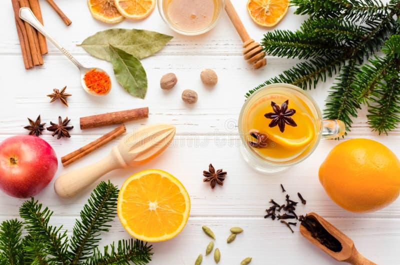 Vin chaud blanc chaud de Noël en verre avec l'orange, le miel, les bâtons de cannelle et l'anis d'étoile avec des ingrédients sur image libre de droits