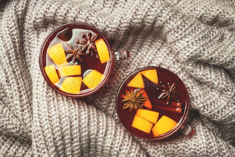 Vin chaud de Noël avec les épices et le fruit sur une couverture tricotée Boisson chaude traditionnelle pour Noël photo stock