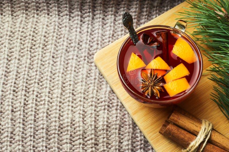 Vin chaud de Noël avec les épices et le fruit sur une couverture tricotée Boisson chaude traditionnelle pour Noël image stock
