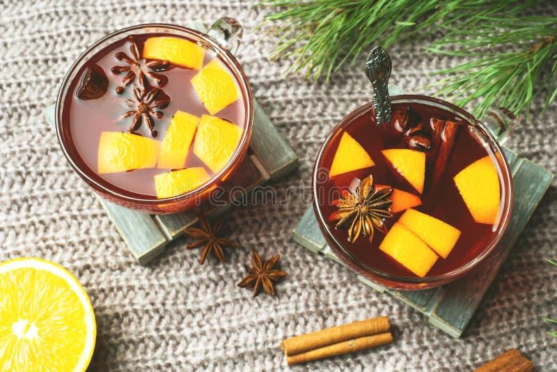 Vin chaud de Noël avec les épices et le fruit sur une couverture tricotée Boisson chaude traditionnelle pour Noël photos stock
