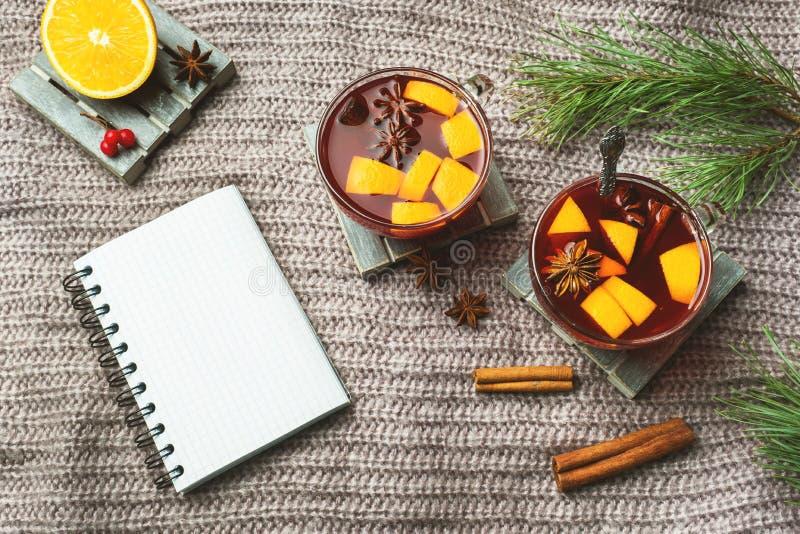 Vin chaud de Noël avec les épices et le fruit sur une couverture tricotée Carnet pour des disques photographie stock