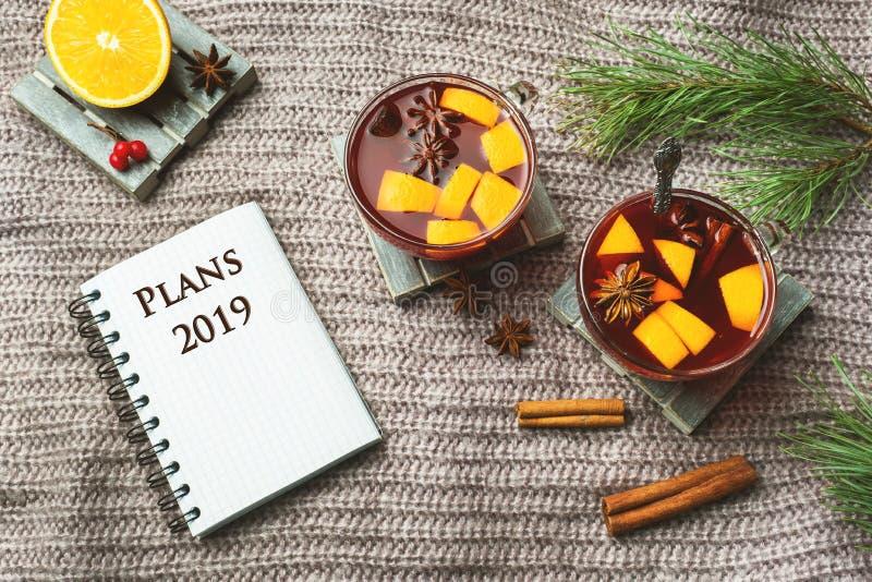 Vin chaud de Noël avec les épices et le fruit sur une couverture tricotée Carnet pour des disques photos stock