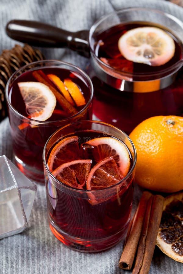 Vin chaud en verres avec l'orange et les épices avec l'écharpe grise images stock
