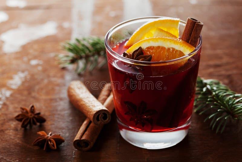 Vin chaud ou gluhwein de Noël avec des épices et des tranches oranges sur la table rustique, boisson traditionnelle des vacances  photo libre de droits