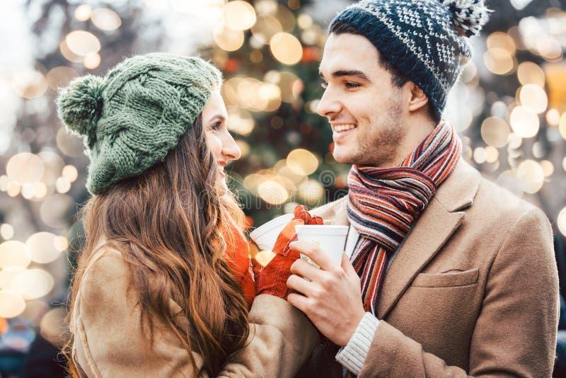 Vin chaud potable de femme et d'homme sur le marché de Noël photographie stock
