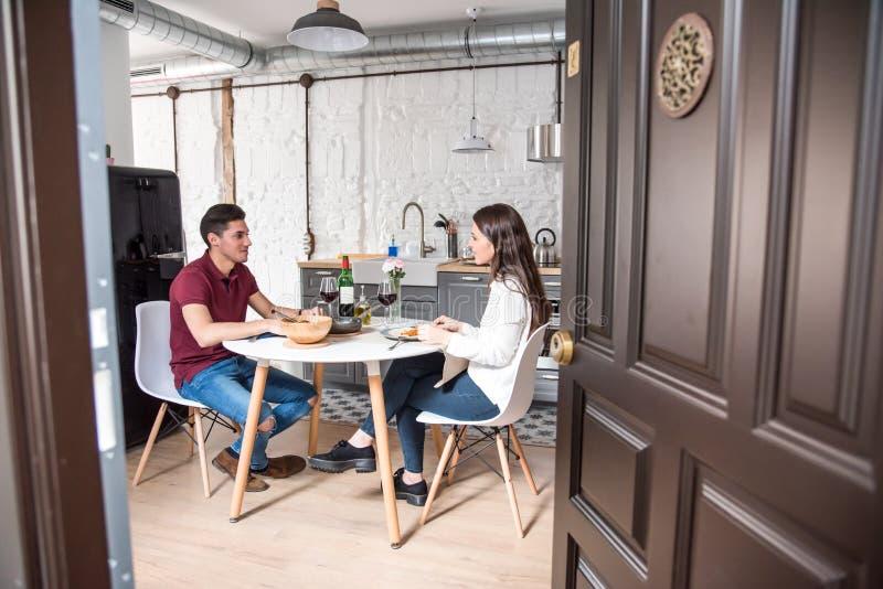 Vin de consommation et potable de jeunes couples heureux à la maison images stock