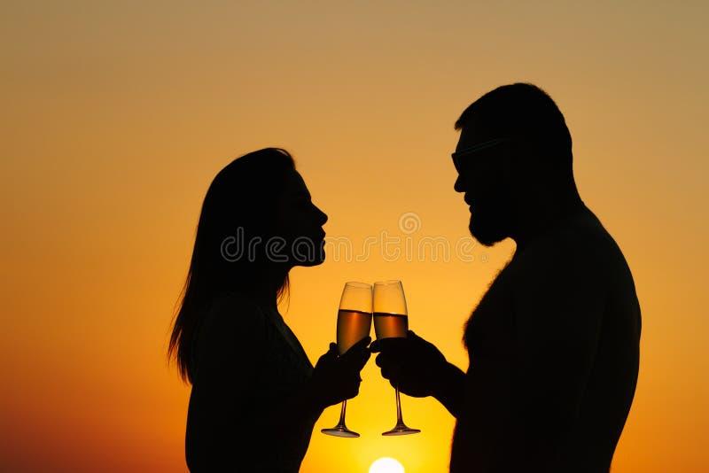 Vin de couples affectueux ou champagne potable pendant le temps de coucher du soleil, silhouette d'un ajouter aux verres à vin su images stock