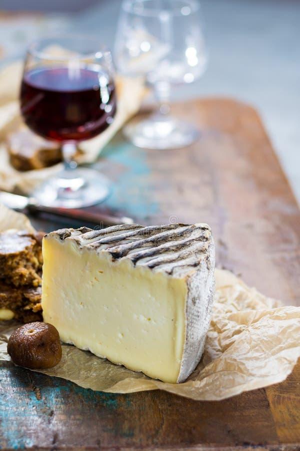 Vin de liqueur doux de dessert en verre, fromage français dur Tomme De image stock
