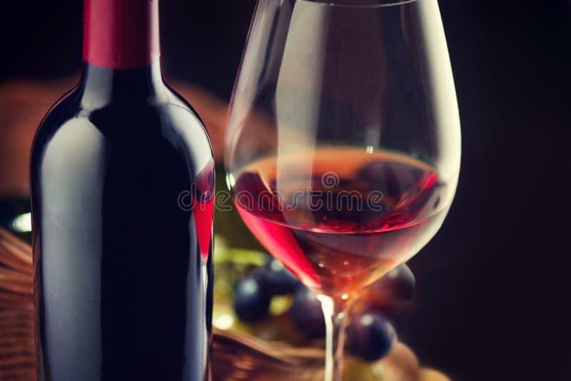 Vin Flaska och exponeringsglas av rött vin med mogna druvor över svart arkivbilder