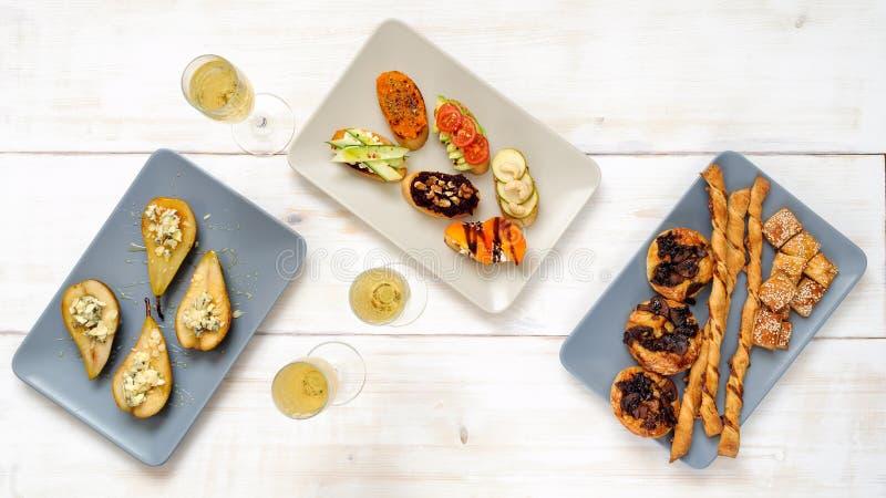 Vin mousseux et casse-croûte sur une table blanche en bois image libre de droits