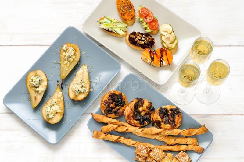 Vin mousseux et casse-croûte sur une table blanche en bois photographie stock