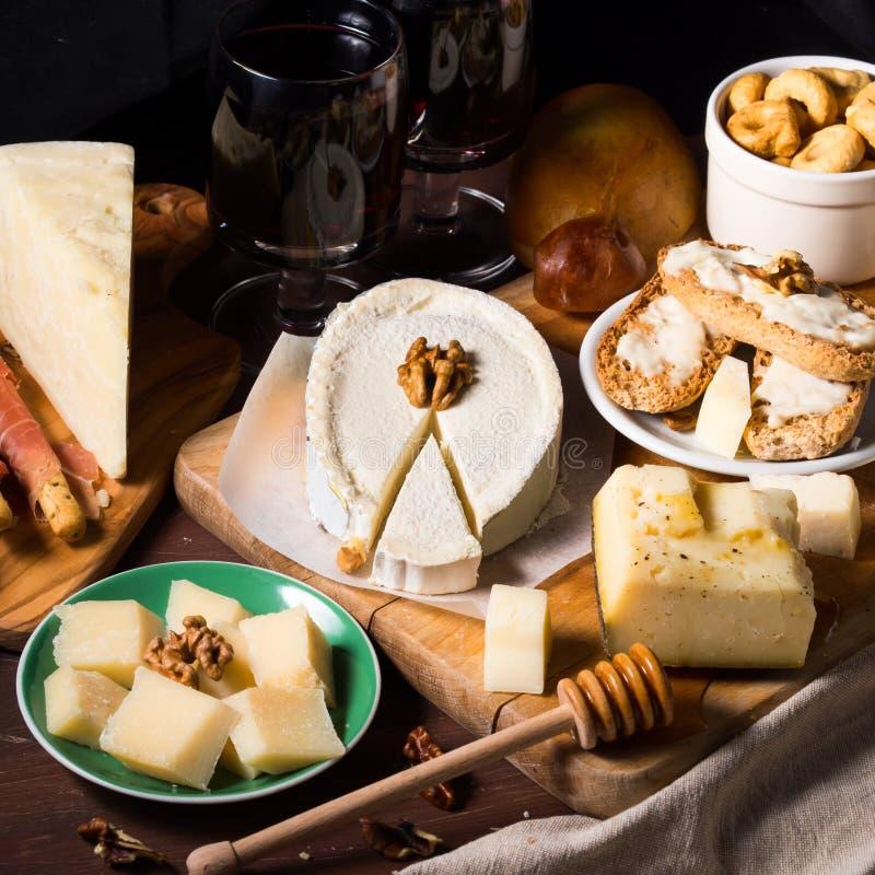 Vin och ost på träbräden Square avbildar royaltyfria foton