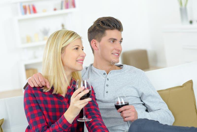 Vin potable de couples dans la maison photographie stock