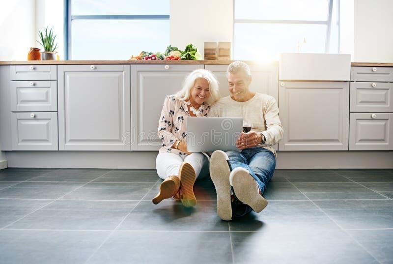 Vin potable de couples supérieurs et à l'aide d'un ordinateur portable à la maison image libre de droits