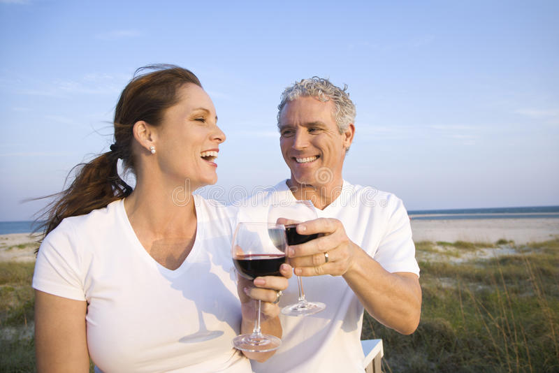 Vin potable de couples sur la plage photo stock