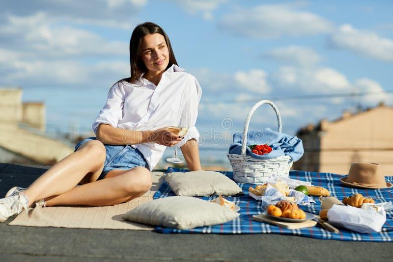 Vin potable de dame songeuse sur le toit de ville photo stock