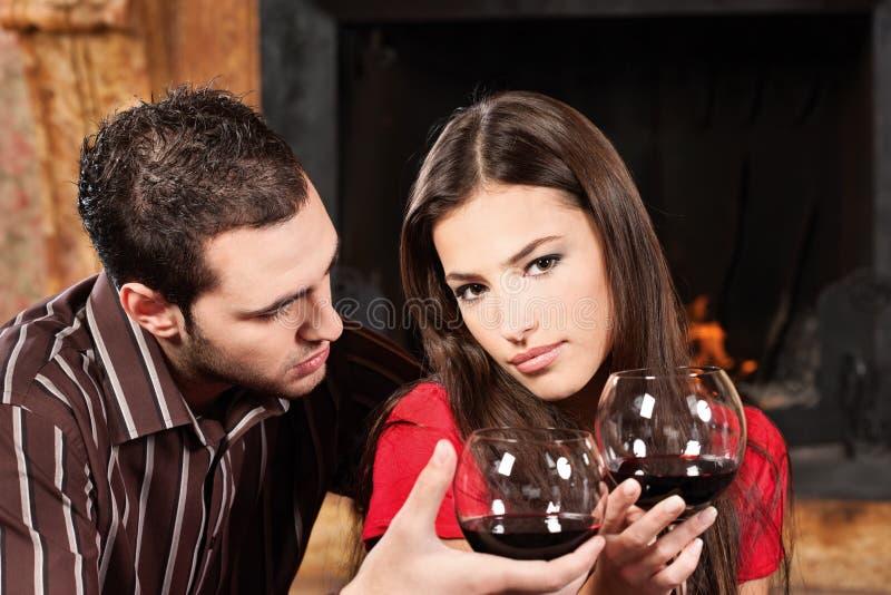 Vin potable de couples près de cheminée photographie stock