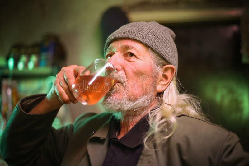 Vin potable de vieil homme photographie stock libre de droits