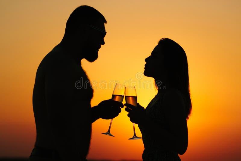 Vin potable ou champagne de couples affectueux pendant le temps de coucher du soleil, sil images stock