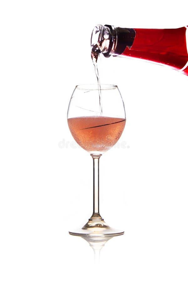 Vin rose de versement dans le verre, d'isolement sur le fond blanc photo stock